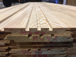 Photo showing Siberian larch planks which have been planed and profiled into a 3 groove profile in the centre of the board.